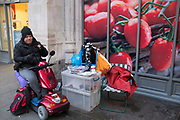 A regular hangs out near Tesco supermarket on Bishopsgate, London, UK. This man comes on his mobility scooter to sit and chat with a Big Issue seller who works this pitch in front of some large tomatoes which are part of fresh produce advertising for the supermarket chain.