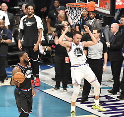 February 17, 2019 - Charlotte, NC, USA - Team Giannis' Stephen Curry, of the Golden State Warriors, comes down after a reverse two-handed dunk, as Team LeBron's LeBron James, of the Los Angeles Lakers, looks on during the 2019 NBA All-Star 2019 game at Spectrum Center in Charlotte, N.C. on Sunday, February 17, 2019. (Credit Image: © David T. Foster Iii/Charlotte Observer/TNS via ZUMA Wire)