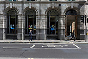 A man on the other side of Old Broad Street, shields his eyes from bright sunlight, on 10th May 2017, in the City of London, England.