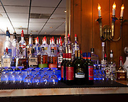 """Variety of liquors at the bar, which is lit by colored lights. Photos at Cunetto's House of Pasta """"On The Hill"""" in south St. Louis taken on Wednesday April 21, 2021 for the Better Business Bureau (St. Louis) Torchlight quarterly magazine. <br />Photo byTim Vizer"""