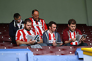 Brentford fans take their seats early and read up on the game. Skybet football league championship match, Burnley  v Brentford at Turf Moor in Burnley, Lancs on Saturday 22nd August 2015.<br /> pic by Chris Stading, Andrew Orchard sports photography.