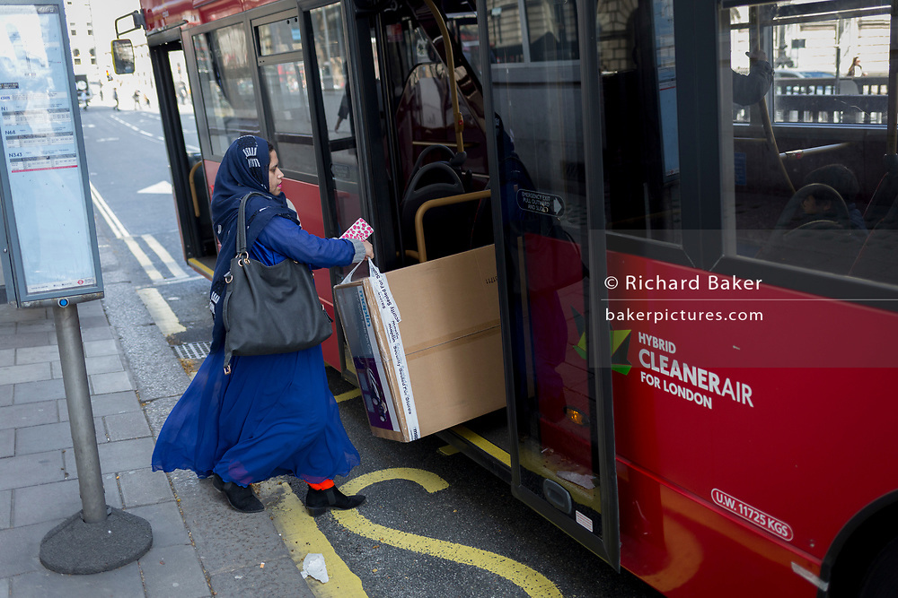 A family load a large box on to a London bus in Aldwych in centrlal London, on 17th April 2018, in London, England.