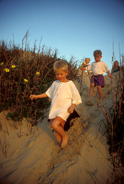Stock photo of children happily descending sand dunes as their mother watches.