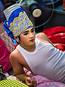 """30 JANUARY 2016 - NONTHABURI, NONTHABURI, THAILAND: A performer relaxes backstage during a """"likay"""" show at Wat Bua Khwan in Nonthaburi, north of Bangkok. Likay is a form of popular folk theatre that includes exposition, singing and dancing in Thailand. It uses a combination of extravagant costumes and minimally equipped stages. Intentionally vague storylines means performances rely on actors' skills of improvisation. Like better the known Chinese Opera, which it resembles, Likay is performed mostly at temple fairs and privately sponsored events, especially in rural areas. Likay operas are televised and there is a market for bootleg likay videos and live performance of likay is becoming more rare.     PHOTO BY JACK KURTZ"""