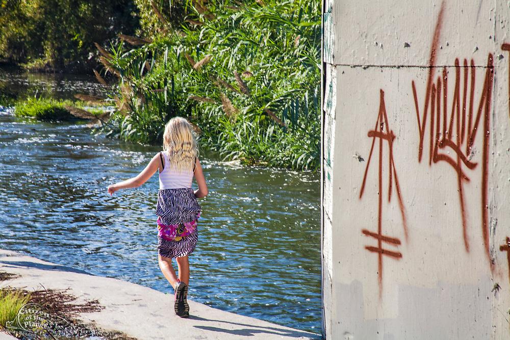 Young girl walking along banks of the Los Angeles River, Glendale Narrows, Los Angeles, California, USA