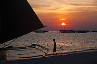Boats silhouetted agains a brilliant orange sunset on the waters off White Sand Beach, Boracay, Philippines.