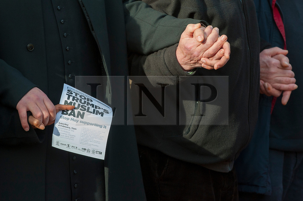 """© Licensed to London News Pictures. 03/02/2017. London, UK. Participants forming a human circle of solidarity hold hands outside Wightman Road mosque in north London during Friday prayers in an event backed by a coalition of faith groups, including members of Reform Judaism, the Christian Muslim Forum and Faiths Forum for London.  The aim is to """"stand with our Muslim brothers and sisters at this time of international turbulence"""", say the organisers. Photo credit : Stephen Chung/LNP"""
