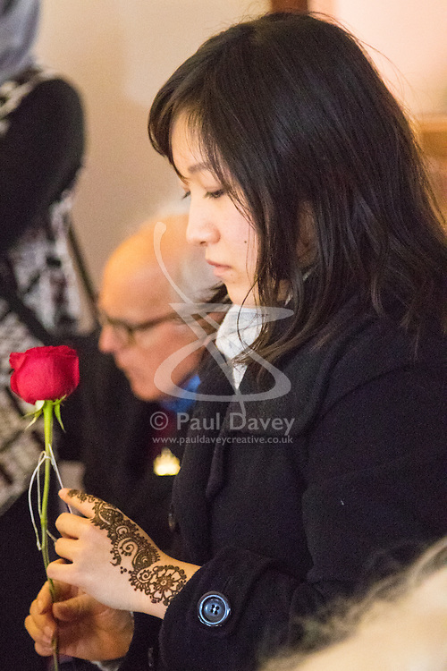 """Finsbury Park Mosque, London, February 7th 2016. A woman reflects with a rose she was given by Muslims during a visit to Finsbury Park Mosque as part of a Visit My Mosque initiative by the Muslim Council of Britain to show non-Muslims """"how Muslims connect to God, connect to communities and to neighbours around them"""".<br /> . ///FOR LICENCING CONTACT: paul@pauldaveycreative.co.uk TEL:+44 (0) 7966 016 296 or +44 (0) 20 8969 6875. ©2015 Paul R Davey. All rights reserved."""