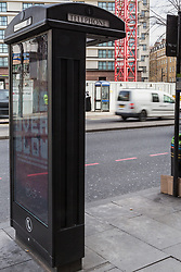 A modern public telephone carrying illuminated advertising is just yards apart from another across the road, adding to the clutter of signs, lampposts, sandwich boards, bus shelters and street furniture on Edgeware Road in London. LONDON, February 12 2019.