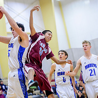 Mancos Bluejay Caden Showalter (25), left, and Ganado Hornet Wacey Benward (32) make contact for a rebound  during the Rehoboth Invitational basketball tournament championship game at Rehoboth High School Saturday.