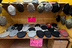 Traditional cloth caps for sale on stall at Barras Market in Gallowgate Glasgow, United Kingdom