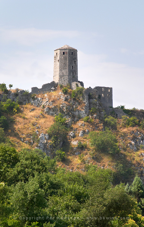 View from the road upstream of the tower and ruined fortress. Pocitelj historic Muslim and Christian village near Mostar. Federation Bosne i Hercegovine. Bosnia Herzegovina, Europe.
