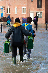 © Licensed to London News Pictures. 24/02/2020. Shrewsbury, Shropshire, UK. People rescue belongings as the River Severn levels continue to rise at Shrewsbury in Shropshire, UK causing severe flood disaster situation. The Environment Agency forecast levels to peak tomorrow evening at around 5.56 metres . the current level at 17.00hrs was 4.95 metres. Photo credit: Graham M. Lawrence/LNP