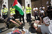 London, UK. Saturday 9th August 2014. Outside an office thought to be used by Tony Blair, protesters lie down on the ground as police guard the premises. Pro-Palestinian protesters in their tens of thousands march through central London to the American Embassy in protest against the military offensive in Gaza by Israel. British citizens and British Palestinians gathered in huge numbers carrying placards and banners calling to 'Free Palestine' and to 'End the seige on Gaza'.