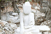 A large marble Buddha under construction at the Sagyin marble mine on 19th March 2016 in Mandalay division in Myanmar. Sagyin, a village 21 miles north of Mandalay is known for its mountain range of seven hills containing marble stone. The marble blocks are carved into Buddha images of different styles and sent to Buddhist monasteries all around Myanmar. Nowadays more work is done by machines, but in the past everything was done by hand