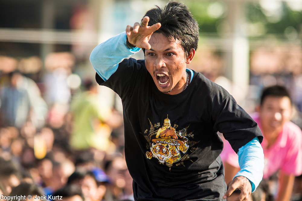 """23 MARCH 2013 - NAKHON CHAI SI, NAKHON PATHOM, THAILAND: A man in a trance and under the power of his tattoo rushes the stage at the Wat Bang Phra tattoo festival. Wat Bang Phra is the best known """"Sak Yant"""" tattoo temple in Thailand. It's located in Nakhon Pathom province, about 40 miles from Bangkok. The tattoos are given with hollow stainless steel needles and are thought to possess magical powers of protection. The tattoos, which are given by Buddhist monks, are popular with soldiers, policeman and gangsters, people who generally live in harm's way. The tattoo must be activated to remain powerful and the annual Wai Khru Ceremony (tattoo festival) at the temple draws thousands of devotees who come to the temple to activate or renew the tattoos. People go into trance like states and then assume the personality of their tattoo, so people with tiger tattoos assume the personality of a tiger, people with monkey tattoos take on the personality of a monkey and so on. In recent years the tattoo festival has become popular with tourists who make the trip to Nakorn Pathom province to see a side of """"exotic"""" Thailand. The 2013 tattoo festival was on March 23.   PHOTO BY JACK KURTZ"""
