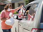 "26 APRIL 2020 - JEWELL, IOWA: MISCHELLE HARDY, hands a bag of ""grab and go"" roast pork dinners to a motorist in Jewell during a fund raiser Sunday. Jewell, a small community in central Iowa, became a food desert when the only grocery store in town closed in 2019. It served four communities within a 20 mile radius of Jewell. Some of the town's residents are trying to reopen the store, they are selling shares to form a co-op, and they hold regular fund raisers. Sunday, they served 550 ""grab and go"" pork roast dinners. They charged a free will donation for the dinners. Despite the state wide restriction on large gatherings because of the COVID-19 pandemic, the event drew hundreds of people, who stayed in their cars while volunteers wearing masks collected money and brought food out to them. Organizers say they've raised about $180,000 of their $225,000 goal and they hope to open the new grocery store before summer.           PHOTO BY JACK KURTZ"