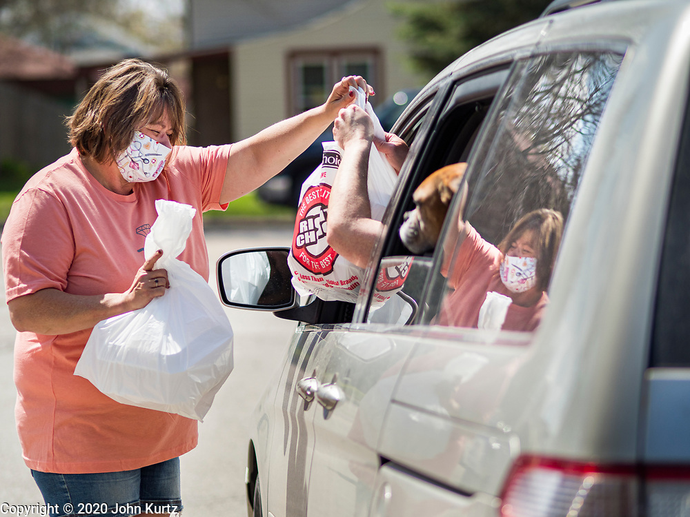 """26 APRIL 2020 - JEWELL, IOWA: MISCHELLE HARDY, hands a bag of """"grab and go"""" roast pork dinners to a motorist in Jewell during a fund raiser Sunday. Jewell, a small community in central Iowa, became a food desert when the only grocery store in town closed in 2019. It served four communities within a 20 mile radius of Jewell. Some of the town's residents are trying to reopen the store, they are selling shares to form a co-op, and they hold regular fund raisers. Sunday, they served 550 """"grab and go"""" pork roast dinners. They charged a free will donation for the dinners. Despite the state wide restriction on large gatherings because of the COVID-19 pandemic, the event drew hundreds of people, who stayed in their cars while volunteers wearing masks collected money and brought food out to them. Organizers say they've raised about $180,000 of their $225,000 goal and they hope to open the new grocery store before summer.           PHOTO BY JACK KURTZ"""