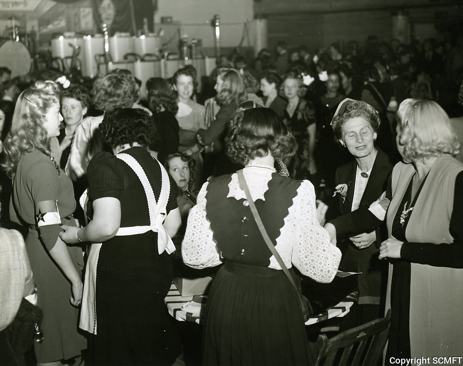 1942 Hostesses have their arm bands attached during the grand opening night at the Hollywood Canteen