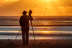 Photographer on beach at sunrise, Gulf of Mexico, Galveston, Texas, USA