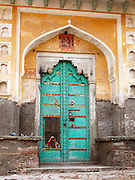 A woman works in a courtyard glimpsed through a partially open door in Amber, Rajasthan.