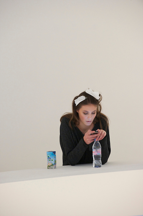 A model spends idle time on her smartphone before the Matthew Williamson autumn 2011 collection at Phillips de Pury Gallery in London on 20 February 2011.