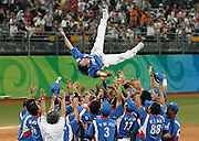 Korea team manager is thrown up in the air to celebrate winning the gold medal in the 2008 Beijing Olympics baseball competition.  Shot for International Baseball Federation.