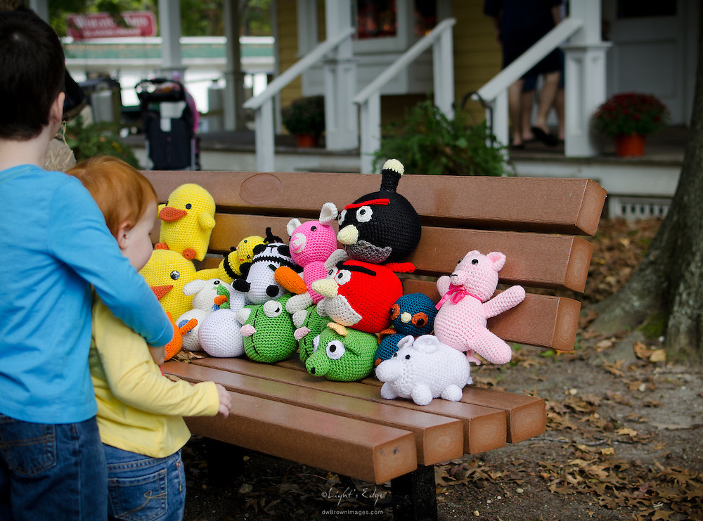 A variety of knitted animals provide a point of curiousity for a youngster at the 2012 Wheaton Arts Fine Craft Fair.