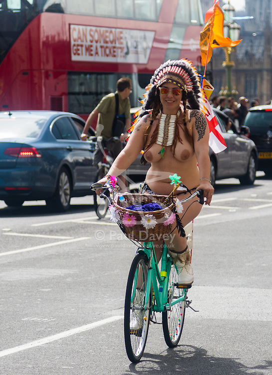 Westminster Bridge, London, June 11th 2016. Hundreds of naked and semi-naked cyclists participate in the World Naked Bike Ride that takes place in cities around the world, to highlight the alternatives to hydrocarbon fuels. PICTURED: A woman with a Native American headers crosses Westminster Bridge.