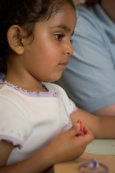 Nursery School girl using crayoning,
