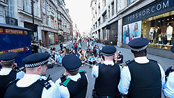 """© Licensed to London News Pictures. 19/04/2019. LONDON, UK.  Police officers block activists trying to run onto Regent Street ahead of the removal of the pink boat at Oxford Circus during """"London: International Rebellion"""", on day five of a protest organised by Extinction Rebellion.  Protesters are demanding that governments take action against climate change.  Police have issued a section 14 order requiring protesters to convene at Marble Arch only so that the protest can continue.  Photo credit: Stephen Chung/LNP"""