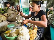 26 OCTOBER 2015 - YANGON, MYANMAR:  A vendor makes noodles dishes for customers on the Yangon Circular Train. The Yangon Circular Railway is the local commuter rail network that serves the Yangon metropolitan area. Operated by Myanmar Railways, the 45.9-kilometre (28.5mi) 39-station loop system connects satellite towns and suburban areas to the city. The railway has about 200 coaches, runs 20 times daily and sells 100,000 to 150,000 tickets daily. The loop, which takes about three hours to complete, is a popular for tourists to see a cross section of life in Yangon. The trains run from 3:45 am to 10:15 pm daily. The cost of a ticket for a distance of 15 miles is ten kyats (~nine US cents), and for over 15 miles is twenty kyats (~18 US cents).     PHOTO BY JACK KURTZ