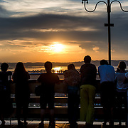 Tourists watch the sunset over the Ayeyarwaddy River from Sutaungpyei Pagoda. Sitting on top of Mandalay Hill, Sutaungpyei Pagoda features a large ornately decorate patio that offers scenic views out over the plain on which the city of Mandalay sits.