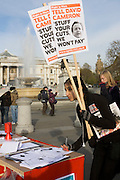 Young female student sign petitiion during protest against government education cuts in Trafalgar Square