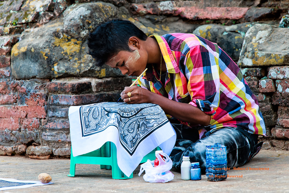 Mirror of Work: A young artist, hard at work, wears a new shirt that roughly mirrors the colours and patterns found in the brickwork that he occupies daily in Bagan, Mayanmar.