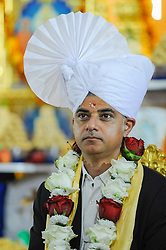 © Licensed to London News Pictures. 28/08/2016. London, UK. Sadiq Khan, Mayor of London, meets global spiritual leader Acharya Swamishree Maharaj and dons a Paag, a special turban reserved for leaders of the community, at Shree Swaminarayan Mandir, a Hindu temple in Kingsbury, north west London.  The Mayor was visiting the temple to thank the congregation for their prayers and blessings during his Mayoral campaign and to celebrate the second anniversary of the mandir. Photo credit : Stephen Chung/LNP