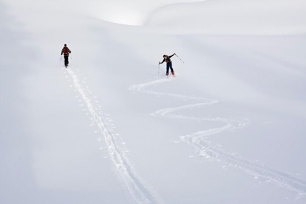 One skier breaks trail in a straight line while another jokingly goes in zigzags in the Mount Baker backcountry along the classic ski tour around Table Mountain, Mount Baker-Snoqualmie National Forest, Washington.