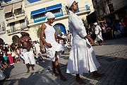 Cuban women of African descent dancing and walking as part of a performance. Performance in Havana old town, local dance and theatre group enacting the slave trade, colonial rule and how African religion and beliefs continuing, becoming what is now Santeria.