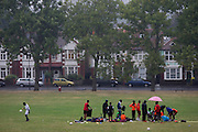 Rain starts falling on a football training session in Ruskin Park, south London. As most players pack their kit away and prepare to leave the field, one last youth player diligently practices his keepie uppies.