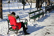 Woman in red coats sits on a bench in Park During Heavy Snowfall In Winter In Bucharest, Romania