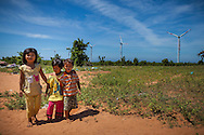 Three barefoot children wander around windfarm land in Ninh Thuan Province, Vietnam<br /> , Southeast Asia