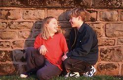 Brother and sister crouching by wall laughing,