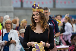 Trafalgar Square, London, June 12th 2016. Rain greets Londoners and visitors to the capital's Trafalgar Square as the Mayor hosts a Patron's Lunch in celebration of The Queen's 90th birthday. PICTURED: A woman gives out cardboard cut-out crowns.