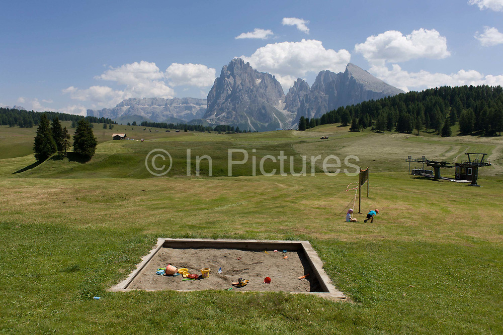 Childrens' sandpit landscape on the Alpe di Siusi (German: Seiser Alm) plateau, above the South Tyrolean town of Ortisei-Sankt Ulrich in the Dolomites, Italy. Walking along one of the dozens of paths, hikers and their children are treated to panoramic views of the peaks and many platy areas to encourage a younger generation into the wilderness. The Alpe di Siusi is the biggest high-alpine pasture in Europe with a surface of 57 km² and its altitude range from 1680 to 2350 m above sea level. This high-alpine pasture is located in the heart of the Dolomites surrounded by the Sasso Lungo Mountain Group, the Sciliar Nature Park, and the Catinaccio Mountain Group, the Northern Alps and the Sciliar Mountain Massif with Santner Peak.