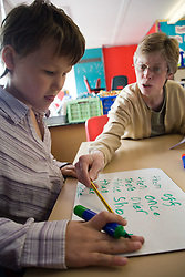 Girl sitting at desk in classroom practising writing skills; with teacher helping,
