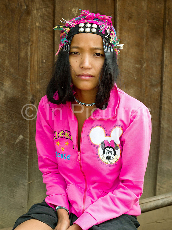 Portrait of Lo Mia, an young Akha Cherpia ethnic minority woman, Ban Nam Hin, Phongsaly province, Lao PDR. She is wearing part of her tradition costume (headwear) and handwoven cotton indigo dyed mini-skirt along with a modern pink Mickey Mouse sweatshirt. One of the most ethnically diverse countries in Southeast Asia, Laos has 49 officially recognised ethnic groups although there are many more self-identified and sub groups. These groups are distinguished by their own customs, beliefs and rituals. Details down to the embroidery on a shirt, the colour of the trim and the type of skirt all help signify the wearer's ethnic and clan affiliations.