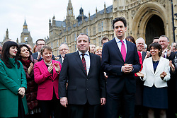 © licensed to London News Pictures. London, UK 24/02/2014. Mike Kane, newly elected Labour MP for Wythenshawe and Sale East being welcomed by Labour MPs as he arrives at the House of Commons with Ed Miliband following his by-election victory. Photo credit: Tolga Akmen/LNP