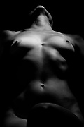Artistic female nude photography with emotive lighting on black background