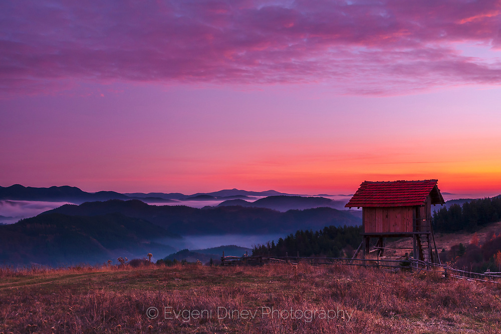 Small wooden shed on a hill at sunrise