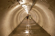 Woman walking through the Greenwich Foot tunnel which links the Isle of Dogs with Greenwich, East London. It was designed by civil engineer Sir Alexander Binnie and opened in 1902.